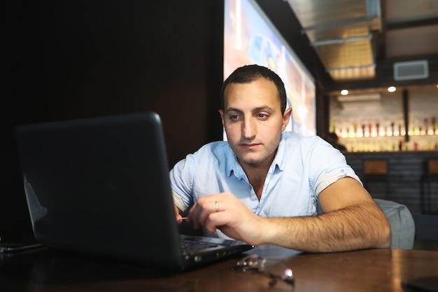 Uomo bello armeno che lavora dietro il computer portatile in caffè