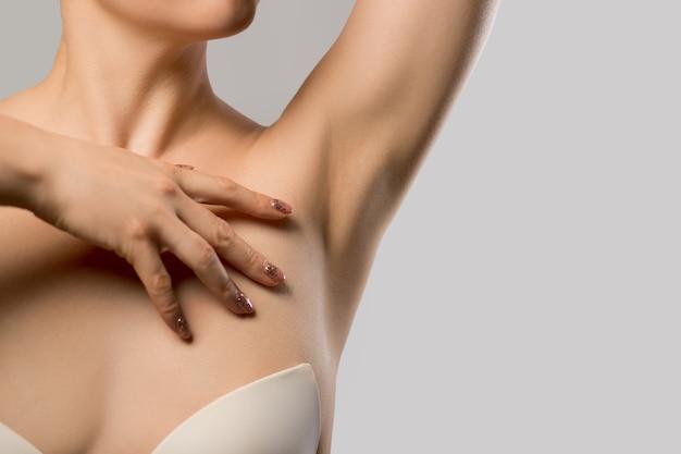 Epilazione delle ascelle, depilazione con lacer. giovane donna che tiene le braccia in alto e mostra le ascelle pulite, depilati su pelle liscia e chiara. ritratto di bellezza. cura della pelle.