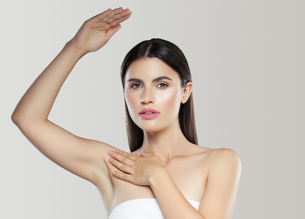 Concetto di deodorante per la pelle pulita di depilazione della donna della mano dell'ascella. colpo dello studio. colore di sfondo.