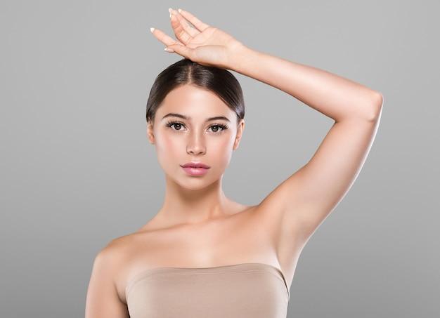Mano della donna di concetto di depilazione della pelle sana dell'ascella della donna in su. sfondo di colore. colpo dello studio.