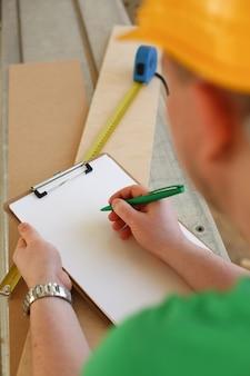 Braccia dell'operaio che prendono le note sulla lavagna per appunti con la penna verde