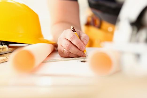 Bracci dell'operaio che fa piano di struttura su carta in scala