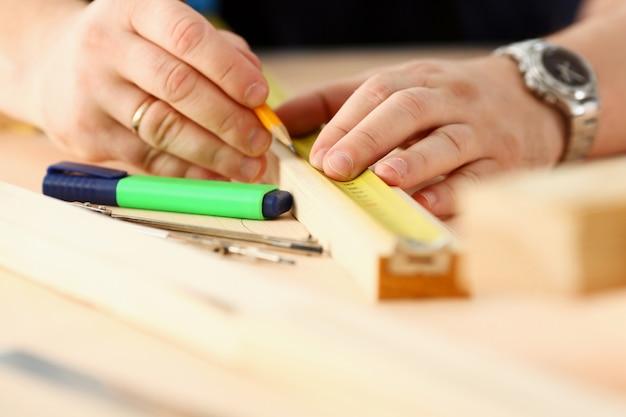 Braccia dell'operaio che misurano il primo piano di legno della barra