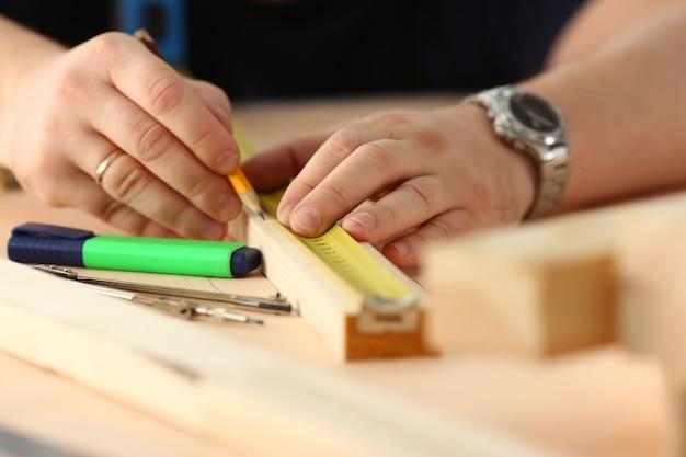 Braccia dell'operaio che misurano barra di legno
