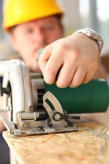 Braccia dell'operaio che usando sega elettrica