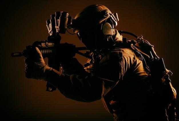 Soldato delle forze d'élite dell'esercito, combattente del servizio di sicurezza speciale in equipaggiamento tattico e munizioni, dispositivo di visione notturna sul casco, mirando fucile a canna corta, furtivamente nell'oscurità, chiave bassa con retroilluminazione rossa