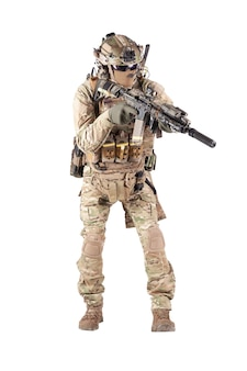 Fante dell'esercito in uniforme mimetica, casco da battaglia, auricolare radio tattico, munizioni extra sul vettore di carico, furtivamente, mirando con mirino laser sul tiro in studio fucile d'assalto isolato su sfondo bianco