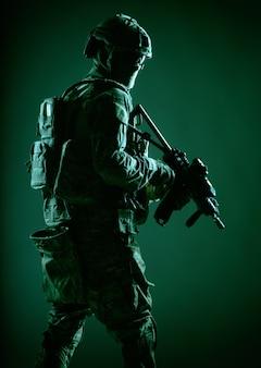 Soldato dell'esercito con elmetto, uniforme da battaglia con munizioni tattiche, nascondendo il viso dietro maschera e occhiali, guardando indietro sopra la spalla, furtivamente nell'oscurità con il fucile di servizio in mano, chiave bassa, riprese in studio
