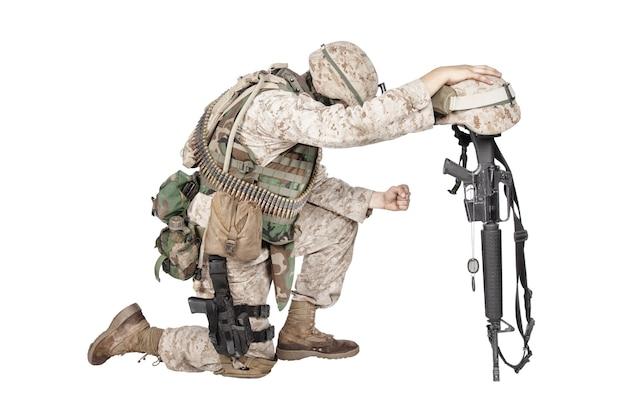 Soldato dell'esercito nel dolore per il compagno caduto, in piedi sulle ginocchia, appoggiato al fucile con il casco e due medagliette sulla catena, riprese in studio isolato su bianco. onori funebri militari, dolore per l'uccisione in azione