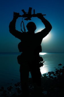 Soldato dell'esercito con il fucile sopra la sua sagoma di luna di notte di testa. concetto di vittoria