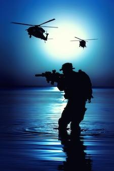 Soldato dell'esercito con la siluetta della luna notturna del fucile sotto la copertura delle tenebre in azione durante il raid che attraversa il fiume nell'acqua. gli elicotteri da combattimento supportano le operazioni aeree
