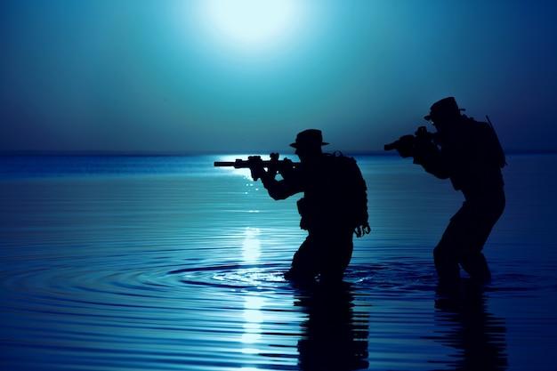 Soldato dell'esercito con la sagoma della luna notturna del fucile sotto la copertura dell'oscurità in azione durante il raid che attraversa il fiume nell'acqua. operazione diversiva segreta