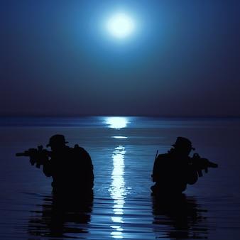 Soldato dell'esercito con la sagoma della luna notturna del fucile sotto la copertura dell'oscurità in azione durante il raid che attraversa il fiume nell'acqua.
