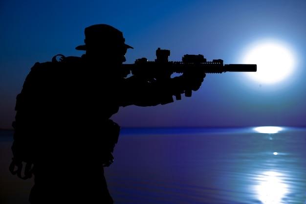 Soldato dell'esercito con la sagoma della luna notturna del fucile sotto la copertura delle tenebre. operazione diversiva segreta