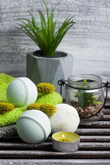 Bombe da bagno aromatiche, asciugamani verdi e piante grasse in spa arrengement sul tavolo di legno marrone