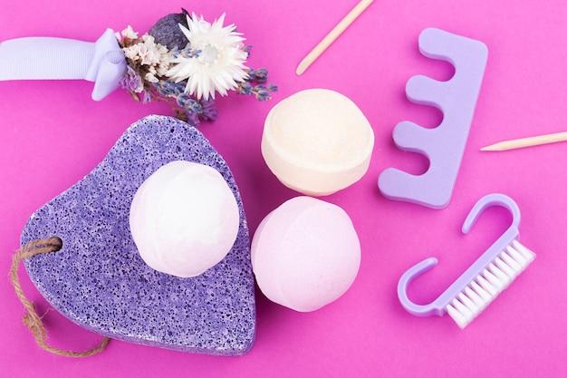 Bombe aromatiche da bagno, pomice viola e lavanda in composizione spa su rosa acceso