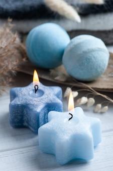 Bombe da bagno aromatiche blu nella composizione spa con fiori secchi e asciugamani