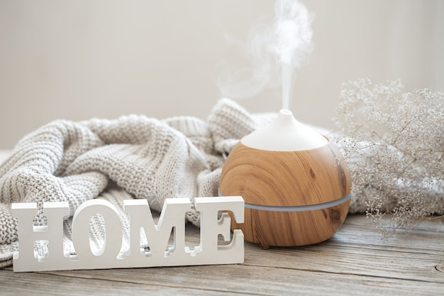 Composizione di aromi con moderno diffusore di oli aromatici su una superficie di legno con un elemento in maglia e una parola decorativa in legno casa.