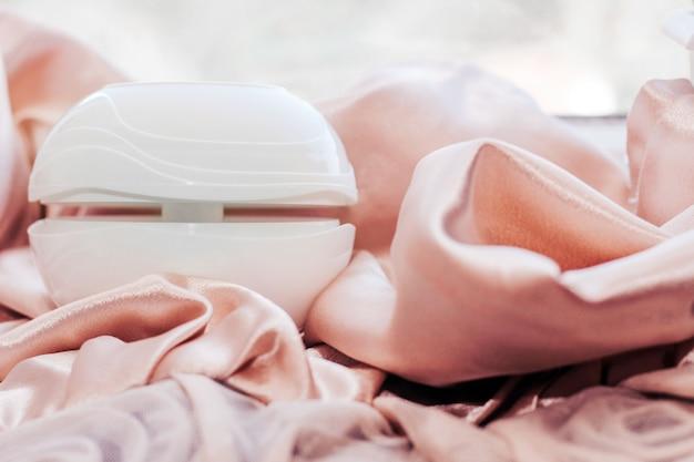Diffusore di aromi per la casa su un motivo in tessuto lucido a forma di rosa.