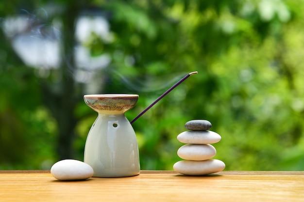 Lampada aromatica con bastoncino di incenso e pietre zen su un tavolo di legno