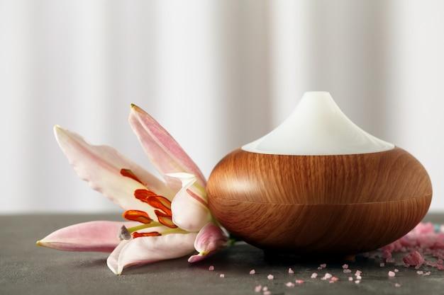 Diffusore di oli aromatici e fiore sul tavolo