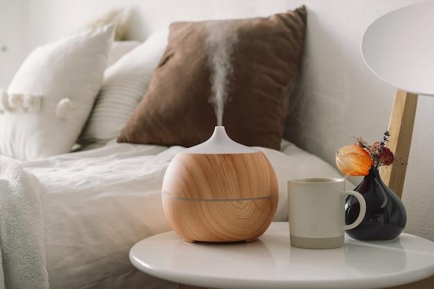 Concetto di aromaterapia. diffusore di oli aromatici su sedia contro in camera da letto. deodorante. diffusore di aromi ad ultrasuoni per la casa