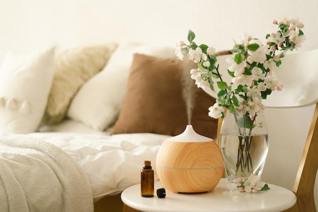 Concetto di aromaterapia. diffusore di oli aromatici su sedia contro in camera da letto