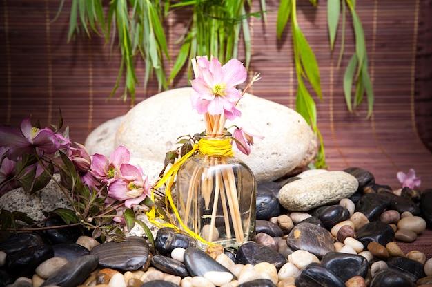 Aromaterapia, spa, trattamenti estetici e benessere con massaggio con pietre, fiori, flacone