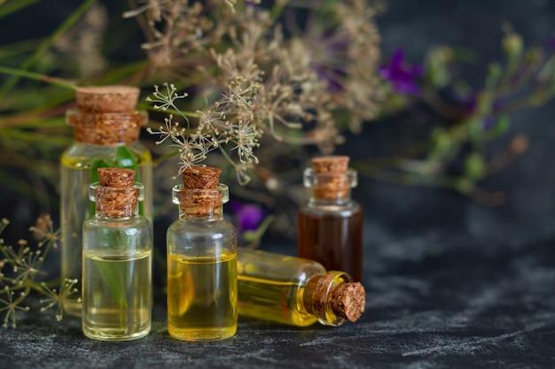 Aromaterapia, spa, massaggi, cura della pelle e concetto di medicina alternativa. oli essenziali di erbe in bottiglie di vetro