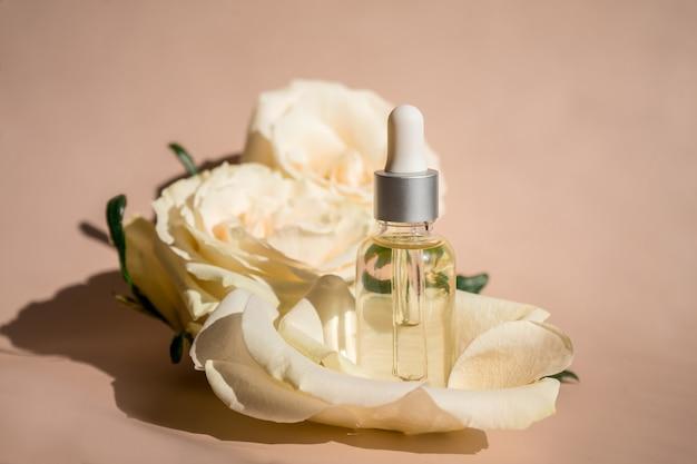 Aromaterapia. fiore bianco e petali, olio essenziale di rosa in bottiglia di vetro. . foto di alta qualità