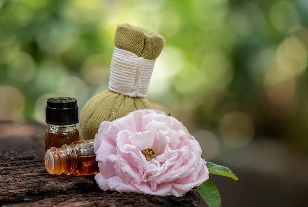 Aromaterapia con fiore di rosa damascena e profumo in impacco alle erbe su foglie verdi bokeh naturale.