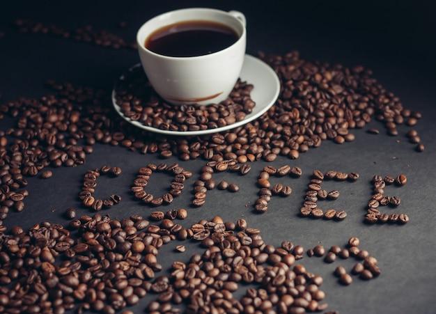 Chicchi di caffè aromatici e una bevanda in una vista superiore grigia della tazza.