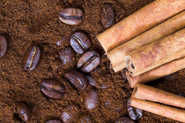 Caffè aromatici e cannella su polvere di caffè macinato, bastoncini di cannella interi e chicchi di caffè e polvere macinata, primo piano