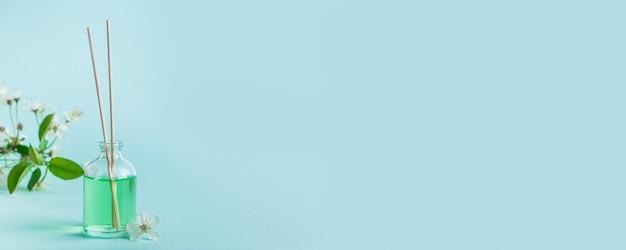 Diffusore aromatico e fiori su fondo blu. spa e concetto di relax. fragranze per la casa. posto per il tuo testo. formato banner