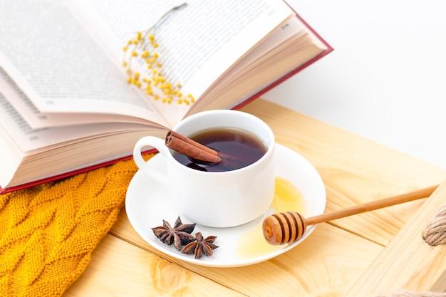 Tè caldo aromatico alla cannella coperto con una sciarpa calda su un fondo di legno di autunno. mestolo di miele con miele. comodo leggere un libro