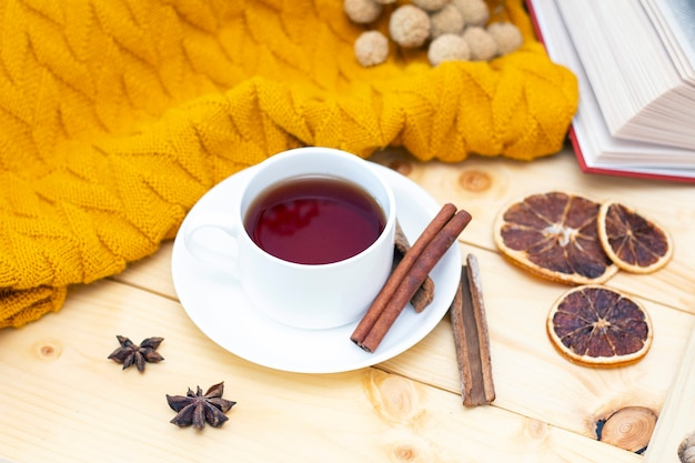 Tè caldo aromatico alla cannella coperto con una sciarpa calda su un fondo di legno di autunno.