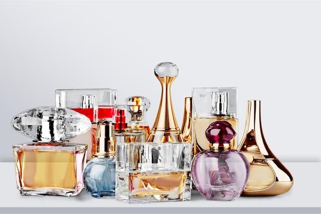 Bottiglie di profumo aromatiche su scrivania in legno bianco su fondo in legno