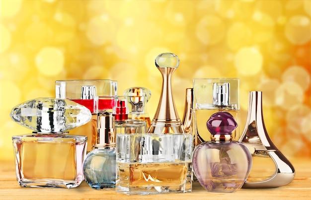 Bottiglie di profumo aromatiche sul tavolo di legno su sfondo sfocato