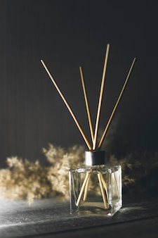 Bottiglia di vetro con diffusore a bastoncini aromatici su sfondo chiaro
