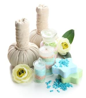 Sali aromatici in bottiglie di vetro e palline di impacco alle erbe per il trattamento termale, su bianco