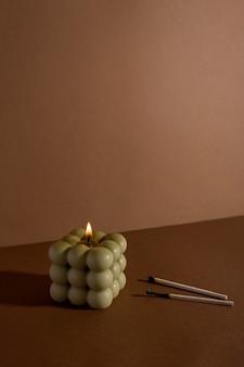Candela profumata aromatica di soia con fumo su sfondo tessile marrone beige moderna candela a bolle ancora...