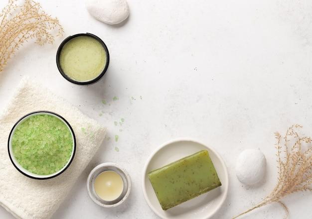 Sale marino aromatico, macchia, sapone alle erbe e asciugamani da bagno su uno sfondo di pietra bianca con candele e pietre. concetto di benessere spa.