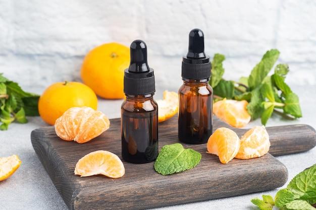 Olio di mandarino aromatico in una bolla scura, olio cosmetico di mandarino su un grigio chiaro