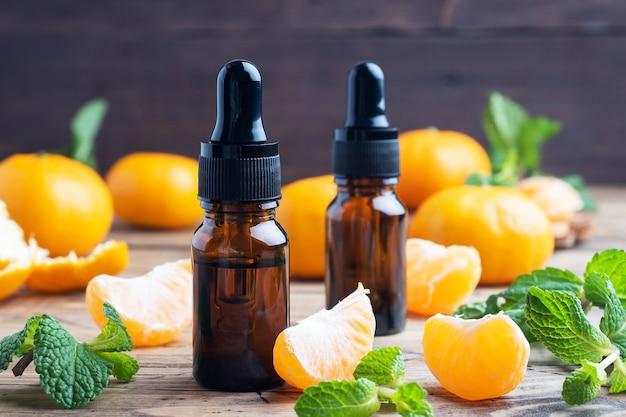 Olio di mandarino aromatico in una bolla scura, olio cosmetico di mandarino su un tavolo di legno, copia dello spazio.