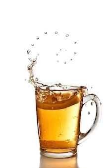 Bolle organizzate di tè e limone sono cadute nella tazza con spruzzata