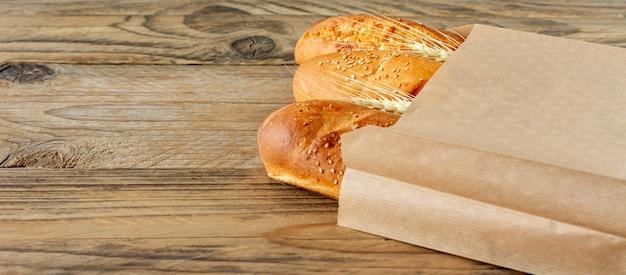 Baguette francesi disposte in sacco di carta e grano sul ripiano del tavolo in legno rustico.