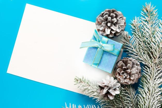 Un arrangiamento di decorazioni natalizie e una confezione regalo. sfondo di natale blu con una cartolina per il testo.