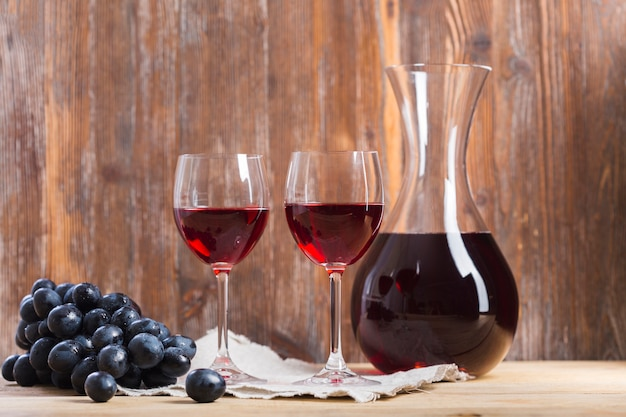 Disposizione di bicchieri e caraffa di vino vista frontale