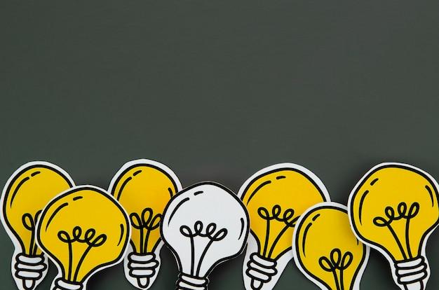 Disposizione del concetto di idea della lampadina su fondo nero