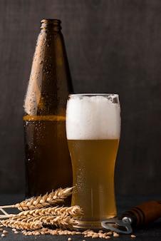 Disposizione con bicchiere di birra e bottiglia